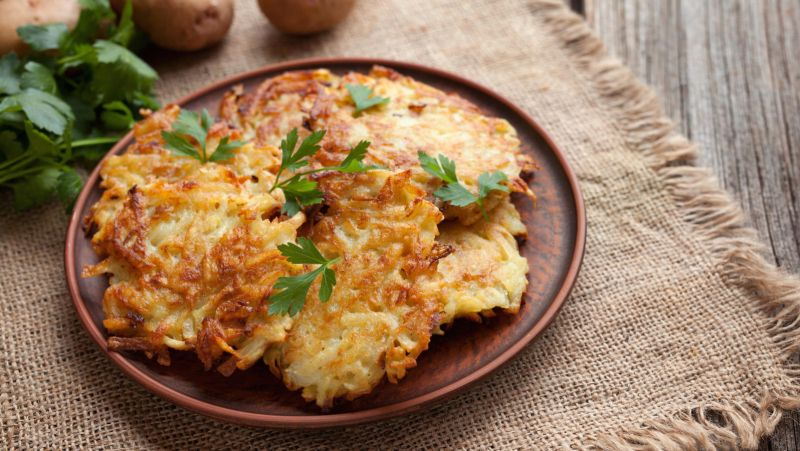 Traditional potato pancakes or latke homemade jewish food Hanukkah celebration recipe. Homemade organic vegan meal in clay dish on vintage wooden background. Rustic style.