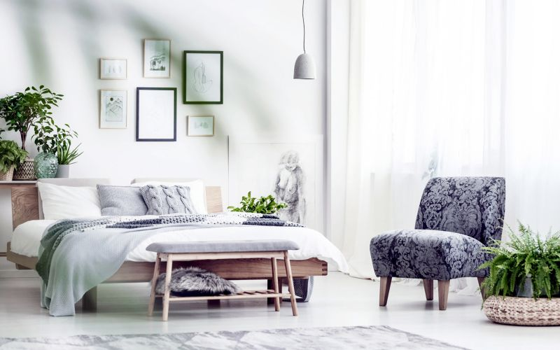 Grey armchair and fern on pouf in bright bedroom with posters and lamp above bed and bench